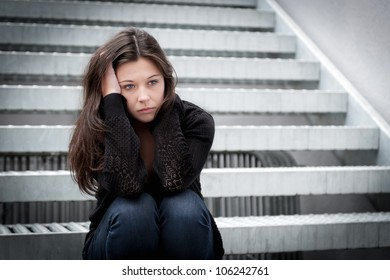 Outdoor portrait of a sad teenage girl looking thoughtful about troubles in front of a stairway