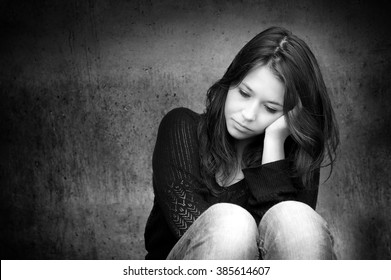 Outdoor portrait of a sad teenage girl looking thoughtful about troubles  in front of a gray wall, copy space on the left side of the image, black and white photo