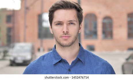 Outdoor Portrait of Sad Young Man Looking at Camera
