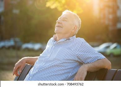 Outdoor portrait of senior man who is enjoying sun.