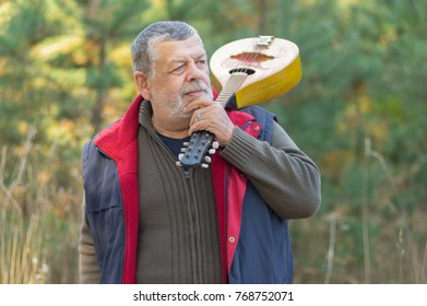 Outdoor portrait of senior musician with mandolin on the shoulder standing against pine forest