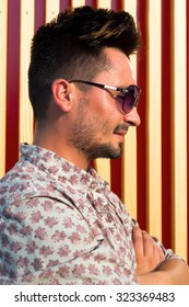 Outdoor Portrait of a serious happy young stylish man at striped background.Trendy portrait of hipster guy with cool hairstyle and tanned skin.Brutal bearded man.Street fashion concept .