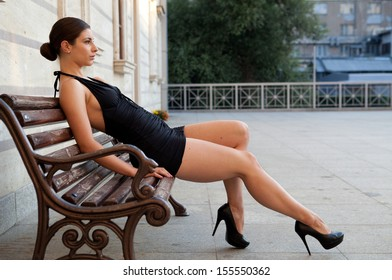 Outdoor portrait of sexy girl in black elegant dress sitting on the bench.