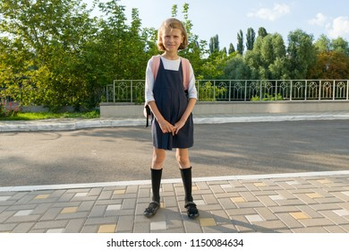 Outdoor portrait of a small student, girl with glasses, uniform with backpack. School, education, knowledge and children