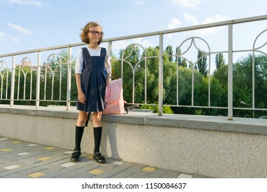 Outdoor portrait of a small student, girl with glasses, uniform with backpack. School, education, knowledge and children, copy space