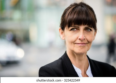 Outdoor portrait of smiling confident senior business woman looking away