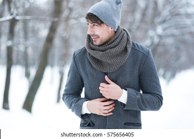 Outdoor portrait of smiling handsome man in coat and scurf. Casual winter fashion