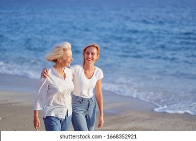 Outdoor portrait of smiling happy caucasian senior mother with her adult daughter hugging and walking on sea beach.