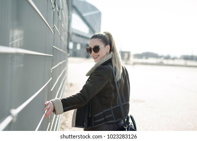 Outdoor portrait of smiling happy woman wearing stylish outfit and walking, sunshine