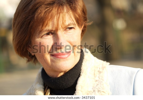 Outdoor portrait of a smiling senior woman in late afternoon sunlight.