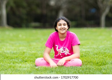 Outdoor Portrait of a Smiling Young Girl Sitting on Grass