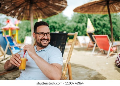 Outdoor portrait of smiling young man on the beach. Drinking cocktail while sitting on a beach chair.