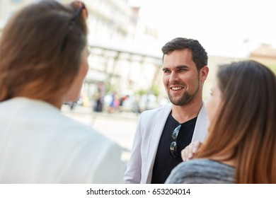Outdoor portrait of smiling young man talking to friends in the city.