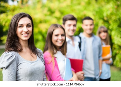 Outdoor portrait of a smiling young student in front of a group of students