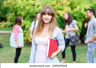 Outdoor portrait of a smiling young woman in front of a group of students