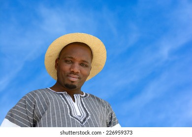 Outdoor portrait of a South African black man with friendly smiling facial expression on a blue sky background.