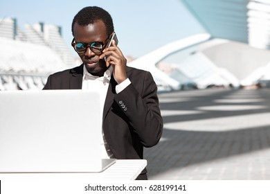 Outdoor portrait of successful confident young African entrepreneur or corporate worker in black suit and stylish shades having phone conversation and working remotely on laptop pc at urban cafe