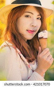 Outdoor portrait in sunflowers garden, teenage asian girl wearing a hat is eating ice cream, vintage tone