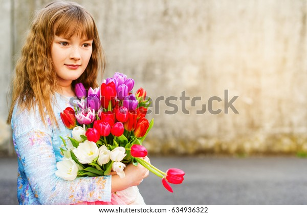 Outdoor portrait of a sweet kid girl with big bouquet of colorful tulips