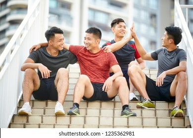 outdoor portrait of a team of four asian young athletes sitting on steps