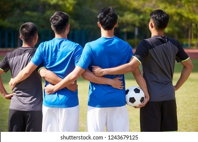 outdoor portrait of a team of young asian soccer football players, rear view