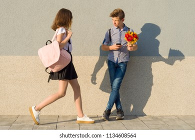 Outdoor portrait of teenagers, boy with bouquet of flowers and girl, gray wall background