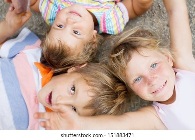 outdoor portrait of three happy children boy and girls upper view