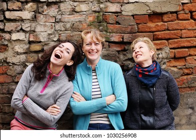 Outdoor portrait of three women standing next to the vintage wall