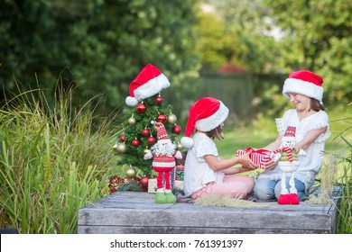 outdoor portrait of two child girls with chritmas tree in green park, christmas in summer, xmas in park