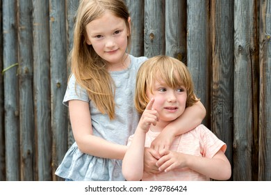 Outdoor portrait of two cute kids, big sister and her little brother against wooden wall