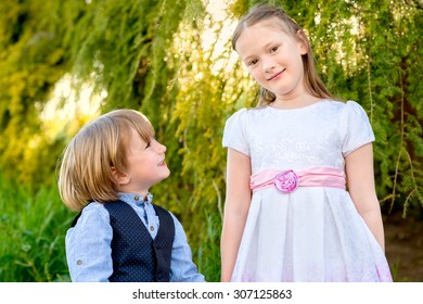 Outdoor portrait of two cute kids playing in the park