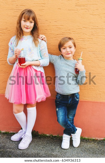 Outdoor portrait of two funny fashion kids, holding drinks, wearing blue and pink clothes