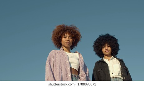 Outdoor portrait of two mixed-race woman with huge afro hair in sky background