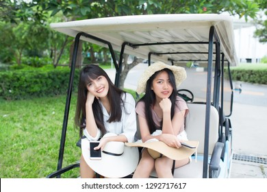 Outdoor portrait of two young asian women sitting on golf cart with happiness