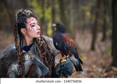 Outdoor portrait of Viking warrior woman in woods wearing war clothes and makeup with face covered in blood holding a hawk in hand. Northern woman with her predator in forest