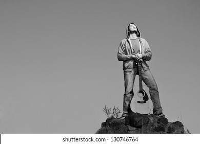 Outdoor portrait of vintage styled guitar man.