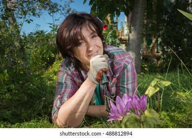 Outdoor portrait of woman during planting flowers in garden