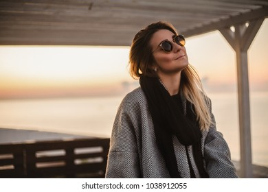 Outdoor portrait woman in sunglasses, stylish grey coat, morning at the sea, woman looking to sunrise, hipster girl posing on camera, pretty face, morning portrait concept, blonde, black scarf, casual