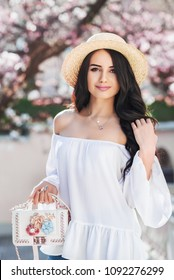 Outdoor portrait of yong beautiful fashionable girl holding small white bag, wearing cold shoulder blouse, straw boater hat. Blooming tree on background. Spring, summer fashion concept.