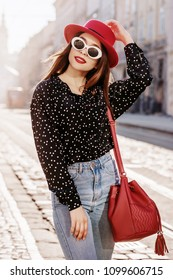 Outdoor portrait of yong beautiful happy smiling woman wearing stylish sunglasses, hat, black polka dot blouse, blue mom jeans, with red bucket bag. Model walking in street of european city