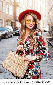 Outdoor portrait of yong beautiful happy smiling woman wearing stylish jumpsuit with floral print, red hat, yellow sunglasses, wrist watch, holding straw bag. Model posing in street of european city