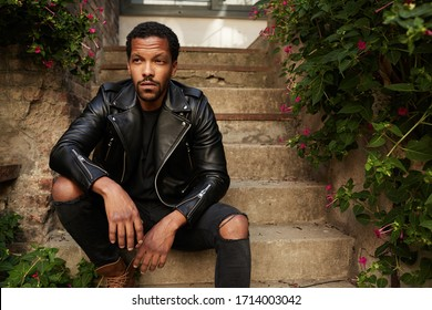 Outdoor portrait of young African man wearing biker leather jacket sitting on stairs. Handsome and confident.