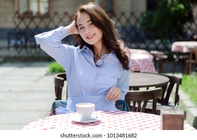 Outdoor portrait of young attractive lady sitting in cafe with perfect smile, romantic style