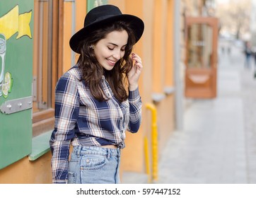 Outdoor portrait of a young attractive lady with curly brunette hair in early spring. Model wearing a checkered shirt and a hat, Mexican-style photo