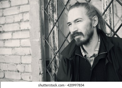 Outdoor portrait of young bearded Asian man in black on gray urban grungy brick wall background, vintage stylized monochrome photo