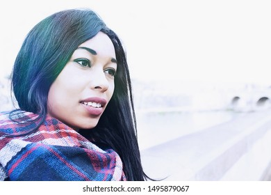 Outdoor portrait of young beautiful afro girl with alluring expression - Beautiful girl with dark skin and long hair taking a walk outside in a cold spring day