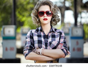 outdoor portrait of young beautiful blonde woman posing on gas station with a lot of petrol pumps on background