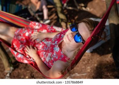 Outdoor portrait of young beautiful blonde cheerful girl enjoy in hammock outdoor. Relaxing in the hammock in the summer garden