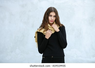 Outdoor portrait of young beautiful brunette woman with wavy long hair stares into camera posing against painted wall