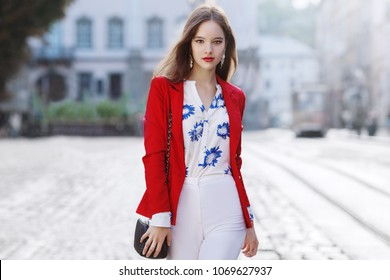 Outdoor portrait of a young beautiful confident woman posing in the street of european city. Model wearing stylish white blouse with flower print, high waist pants, red jacket.  Female fashion concept